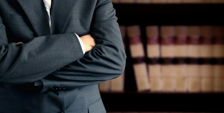 Man in suit with arms cross inform of law books
